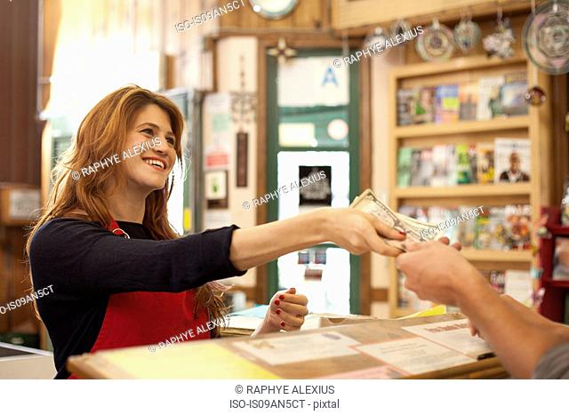 Female shop assistant taking cash payment in health food store