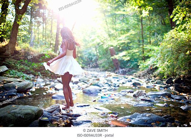 Glamorous young woman wearing white dress stepping over forest river rocks