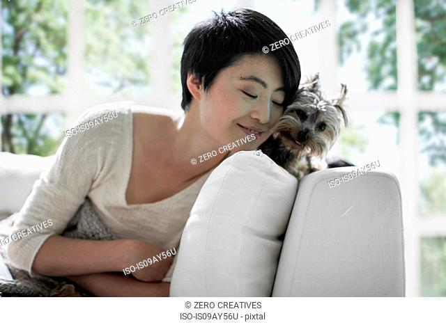 Woman snuggling up to pet dog on sofa