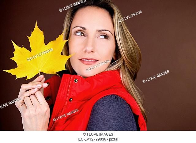 A mid adult woman holding an autumn leaf