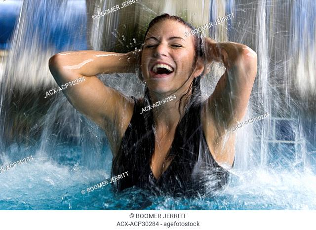 A young woman enjoys a dip in the water fountain at the Kingfisher Resort and Spa in Courtenay. The Comox Valley, Vancouver Island, British Columbia, Canada