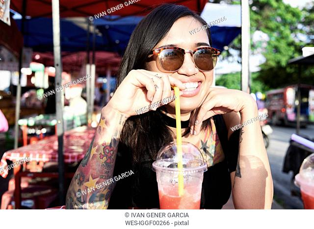 Portrait of happy woman drinking a smoothie outdoors