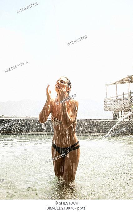 Woman splashing in pool outdoors