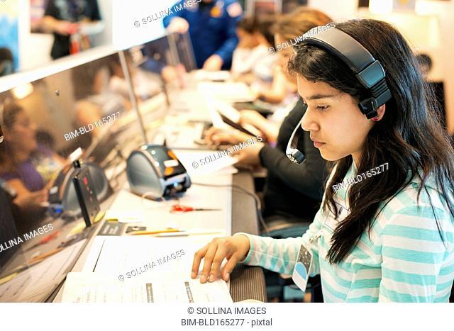 Hispanic student listening to headset at desk