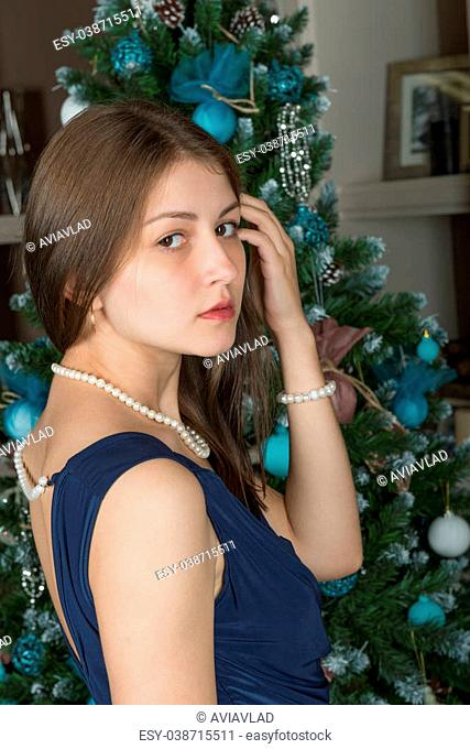 Portrait of a cute girl with beautiful long straight hair in a blue dress on a background decorated Christmas tree