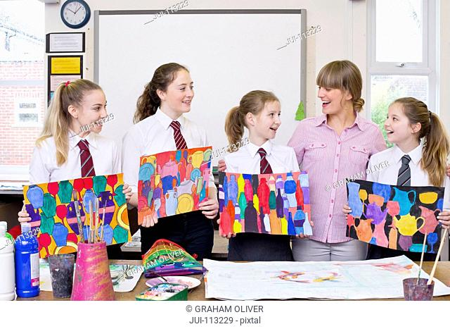 Smiling art teacher and middle school students showing paintings in art class