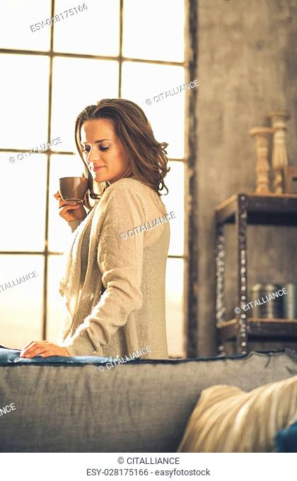 A brunette woman in comfortable clothing is is smiling and holding a hot cup of coffee, looking down. Industrial chic background, and cozy atmosphere
