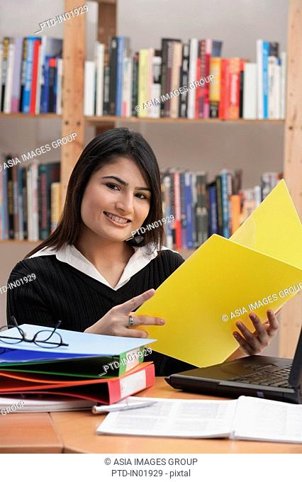 Woman in library, holding yellow folder