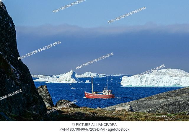 23 June 2018, Denmark, Greenland, Ilulissat: A small ship passes between icebergs near the coastal town of Ilulissat in western Greenland.