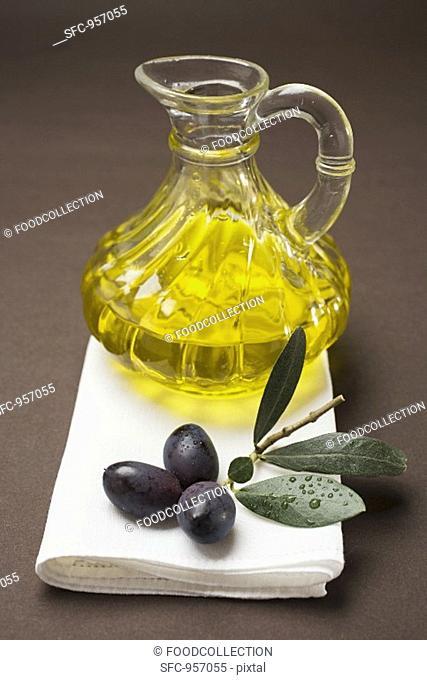 Olive sprig with black olives, carafe of olive oil behind