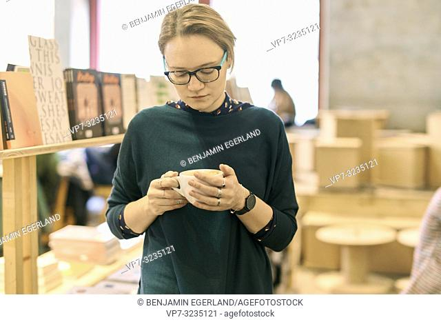 woman holding coffee cup indoors in book store café, in Munich, Germany