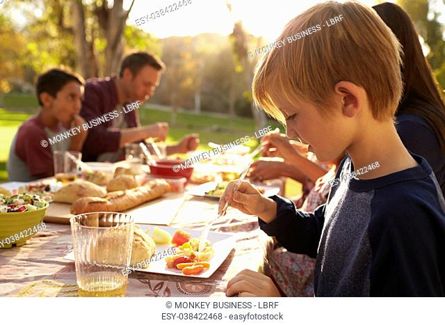 Young boy eating at a picnic table in a park