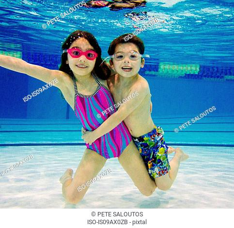 Boy and girl underwater in swimming pool wearing goggles looking at camera smiling
