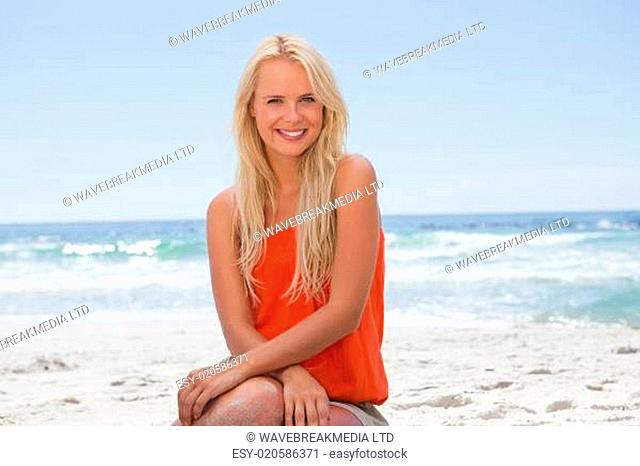 Smiling young woman sitting down in front of the ocean