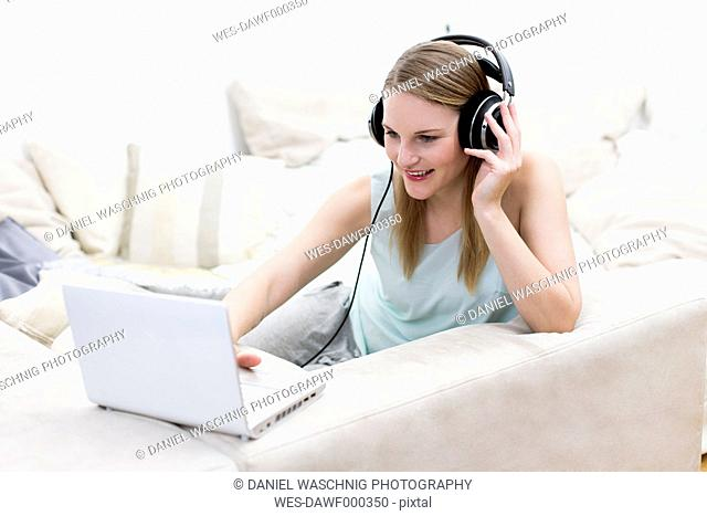 Portrait of woman sitting on a couch using headphones and laptop