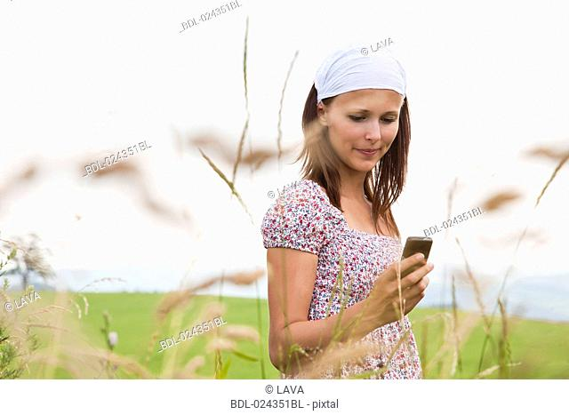 portrait of young woman checking moile phone for text messages