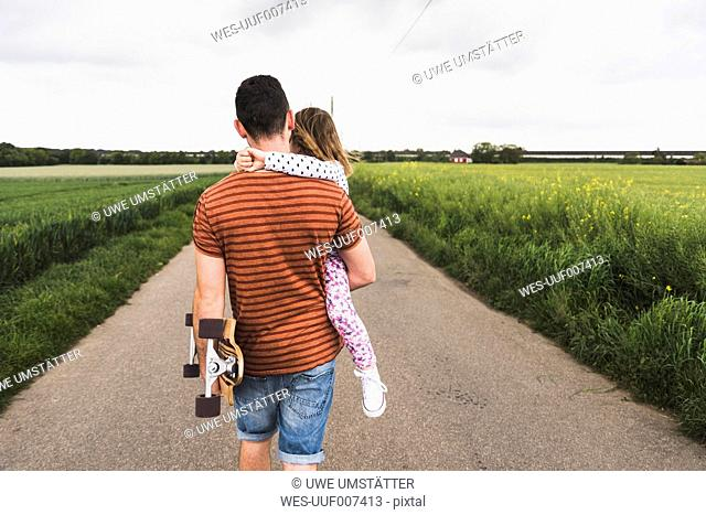 Father with skateboard carrying daughter on country lane