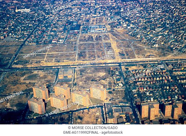 Aerial view facing north of the neighborhoods of Rego Park, Elmhurst, and Corona, Queens, New York City, 1957. The Long Island Expressway (LIE) runs...
