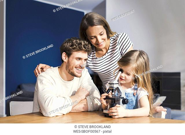 Parents watching daughter use a microscope, smiling proudly