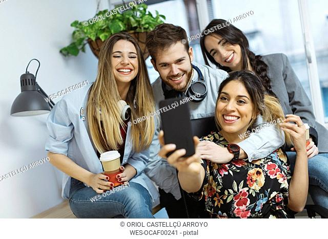 Happy casual coworkers in the office taking a selfie