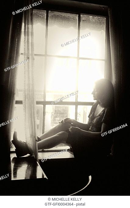 Profile of Beautiful Woman Sitting on Window Ledge