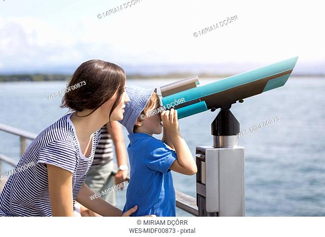Germany, Friedrichshafen, Lake Constance, mother with son looking through telescope at lakeshore