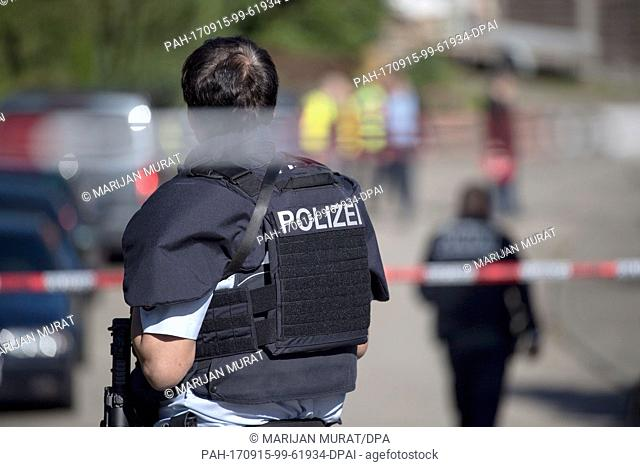 A police officer standing behind a cordon near the crime scene in Villingendorf, Germany, 15 September 2017. A man, a woman and a 6-year-old boy have been shot...