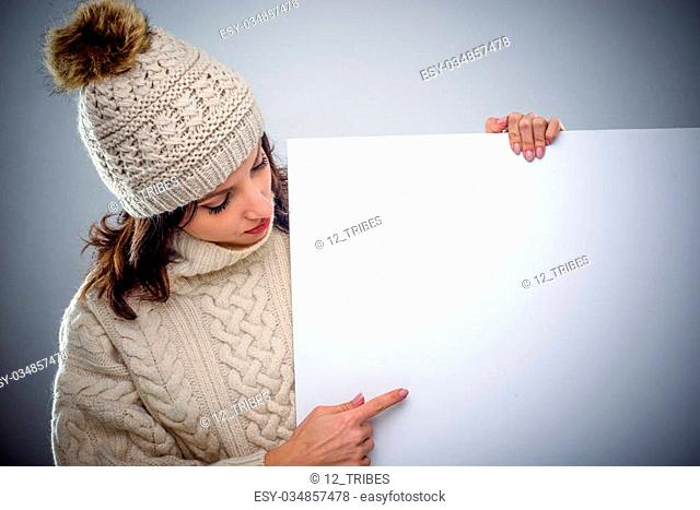 Young woman in winter fashion pointing to a blank white sign or placard she is holding in her hand as she draws your attention to the copy space