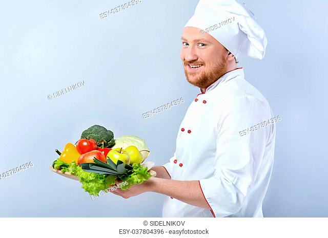 Side view photo of positive young male chef in white uniform. Head-cook cheerfully smiling, looking at camera and holding big plate of fresh vegetables