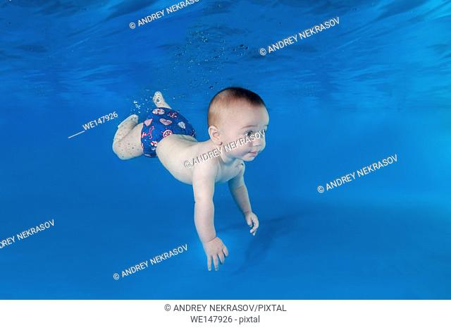 6 months infant boy learning to swim underwater in waterbaby class in the pool