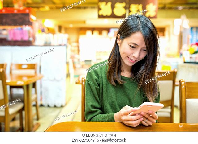 Woman using cellphone in japanese restaurant