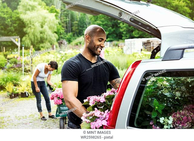 Car parked at a garden centre, a man loading flowers into the boot