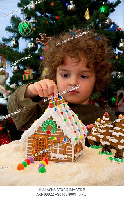 Young boy plays with a gingerbread log cabin with Christmas tree in the background