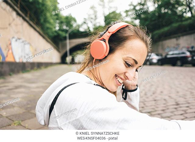 Smiling sportive young woman wearing headphones outdoors