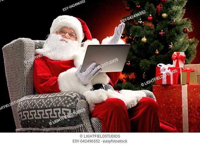 Santa Claus sitting on grey armchair using laptop and gesturing
