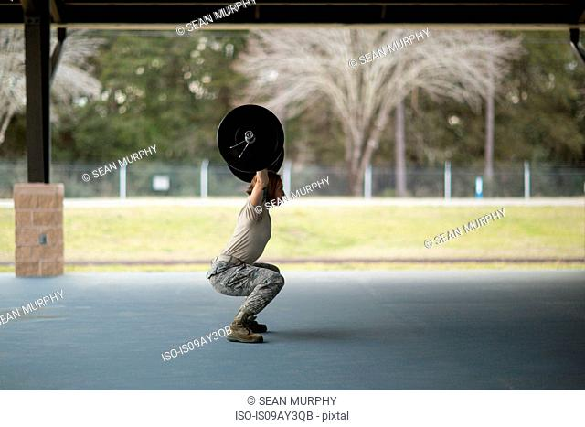 Female soldier squatting weight lifting barbell at military air force base