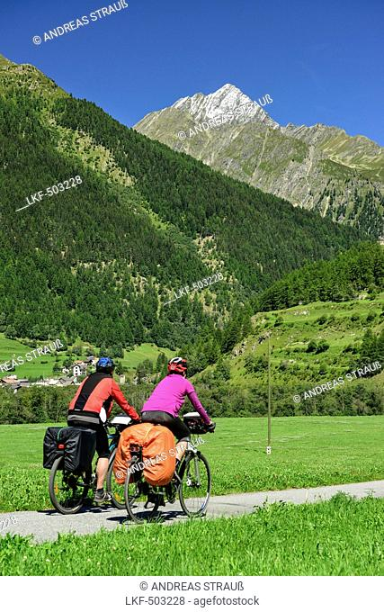 Two cyclist passing Inn cycle route towards Piz Linard, Lavin, Lower Engadin, Canton of Graubuenden, Switzerland