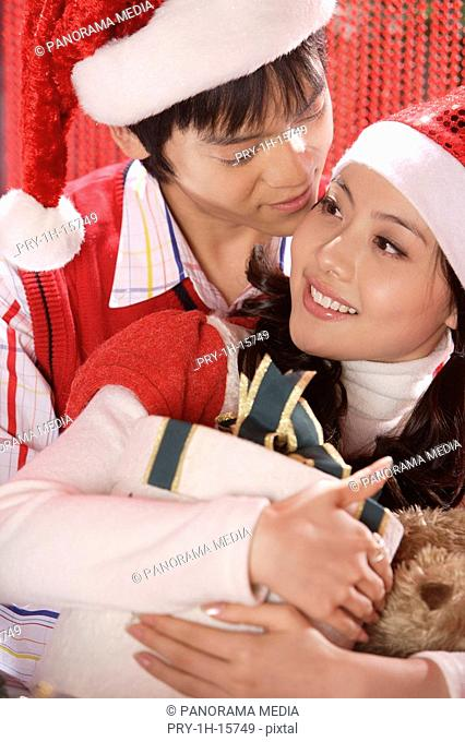 Young couple embracing together in Christmas hats