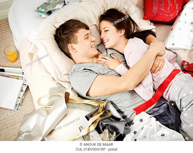 Couple in bed laughing, with presents
