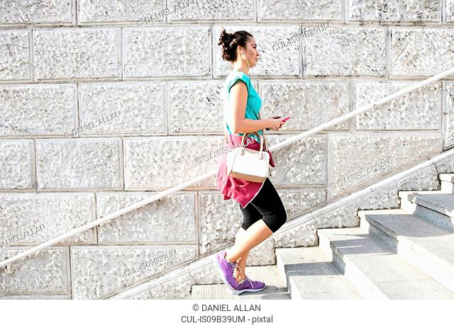Young woman wearing sports clothing and earphones, walking up steps