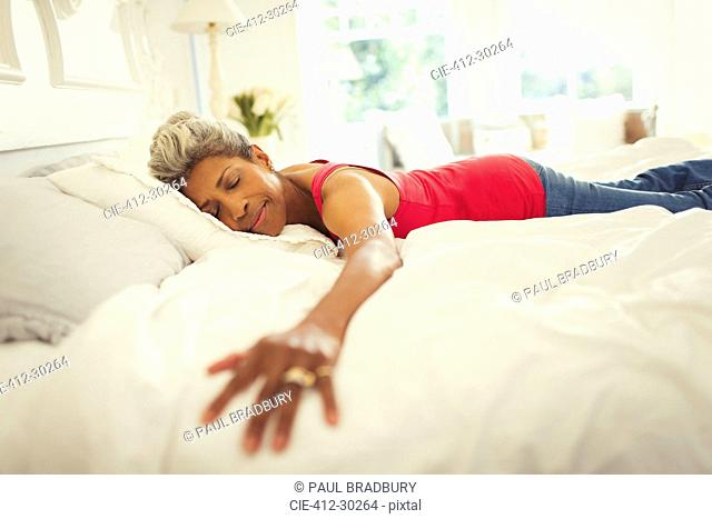 Serene mature woman laying on bed with arms outstretched