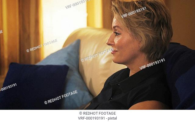 Dolly shot of woman relaxing on sofa in the evening, turning and laughing