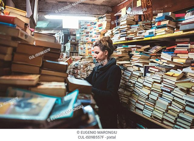 Young woman browsing in stacked book shop, Venice, Italy