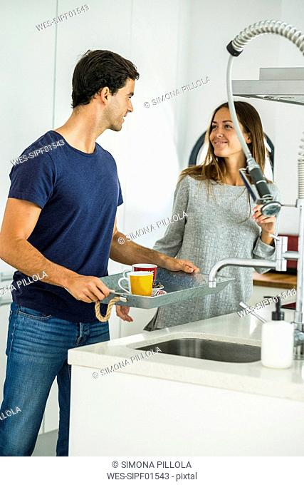 Young couple with coffee cups on tray in kitchen