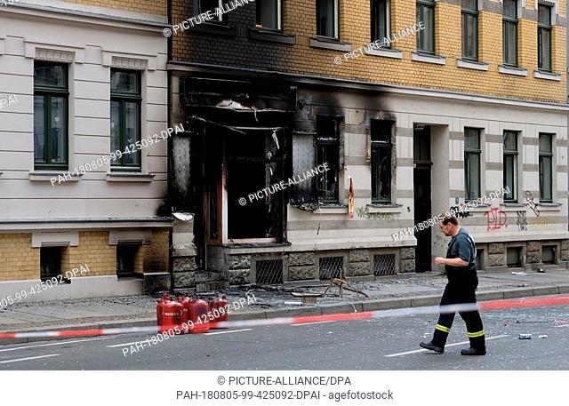 05 August 2018, Germany, Leipzig: A policeman passes an apartment building in which an explosion occurred. There was a detonation in the doner kebab snack bar...