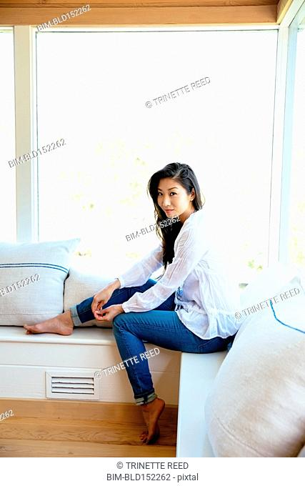 Chinese woman smiling on window bench