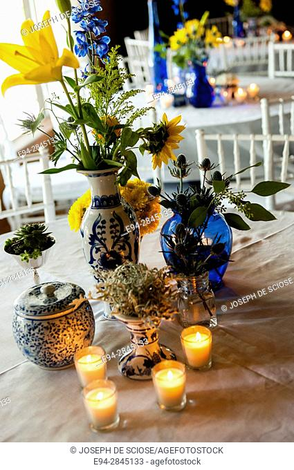 A colorful table display of cut flowers in vases and votive candles