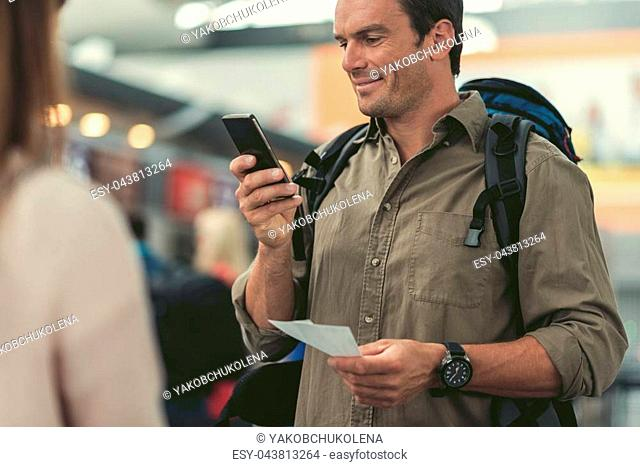 Always online. Positive bristled man is standing with tickets and looking at screen of smartphone with smile while sending message to his friends