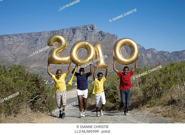 Jumping boys holding balloons shaped in numbers 2010, with South African flag, Table Mountain in background, Cape Town, Western Cape Province, South Africa