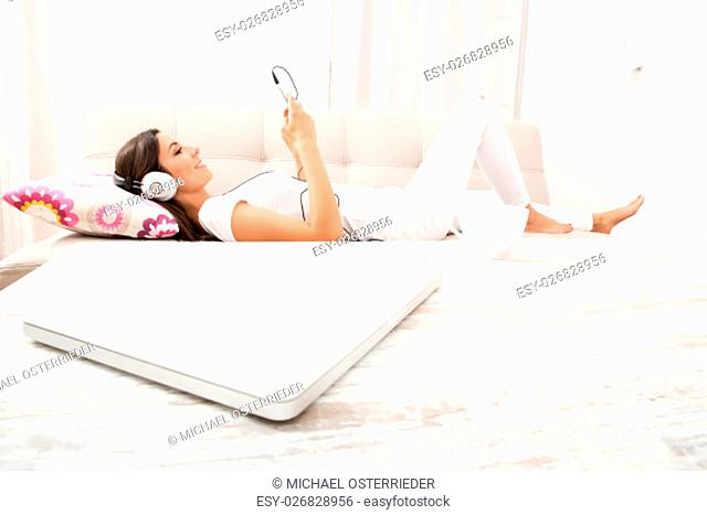 Portrait of a beautiful young woman laying on the couch in headphones, listening to music with her smarthphone
